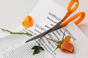 A scissor cutting a marriage certificate, divorce lawyers