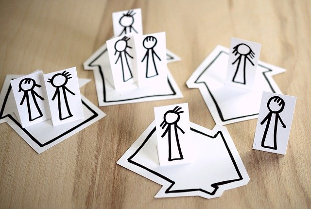 Paper cut of people standing on their own house
