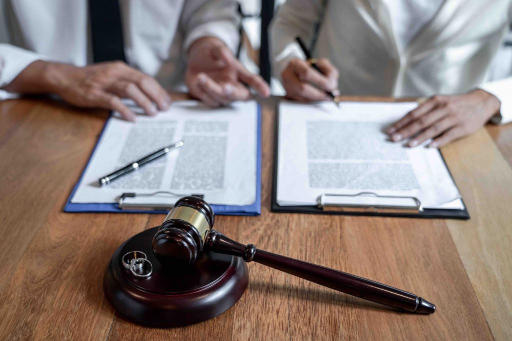 Judge gavel and two golden marriage ring, Contract decree of divorce (dissolution or cancellation) of marriage, husband and wife during divorce process and signing of divorce contract