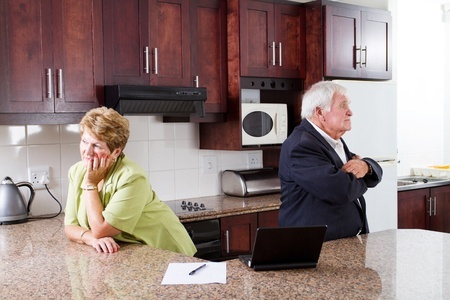 Elderly couple stand against each other with a paper on table