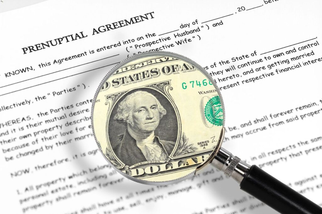 prenuptial agreement with a magnifying glass with dollar bill image in it