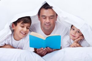 Dad reading a book for his two kids, parenting time