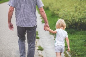 Backview of a father with his kid walk together
